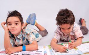 jumeaux allongés sur le sol pour faire leurs devoirs